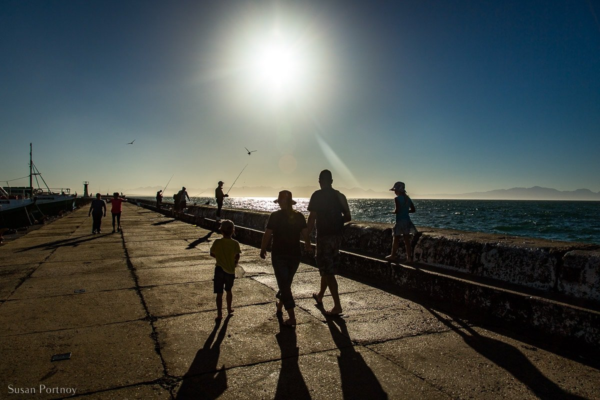 Silhouettes of a family waling on a jetty towards the sun
