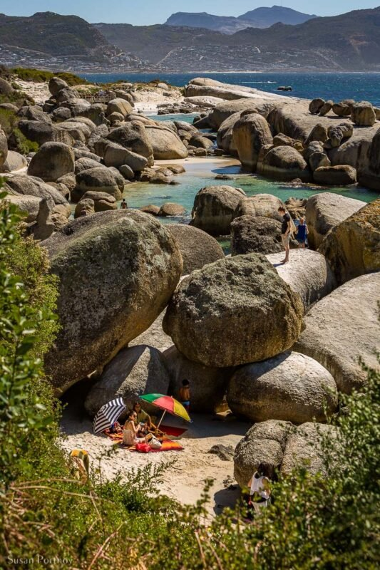 A view of swimmers on Boulders Beach with an  umbrella and towel