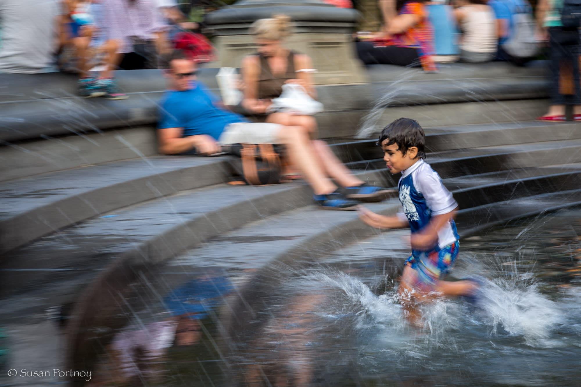 Little boy runs into the fountain in Washington Square Park, NYC
