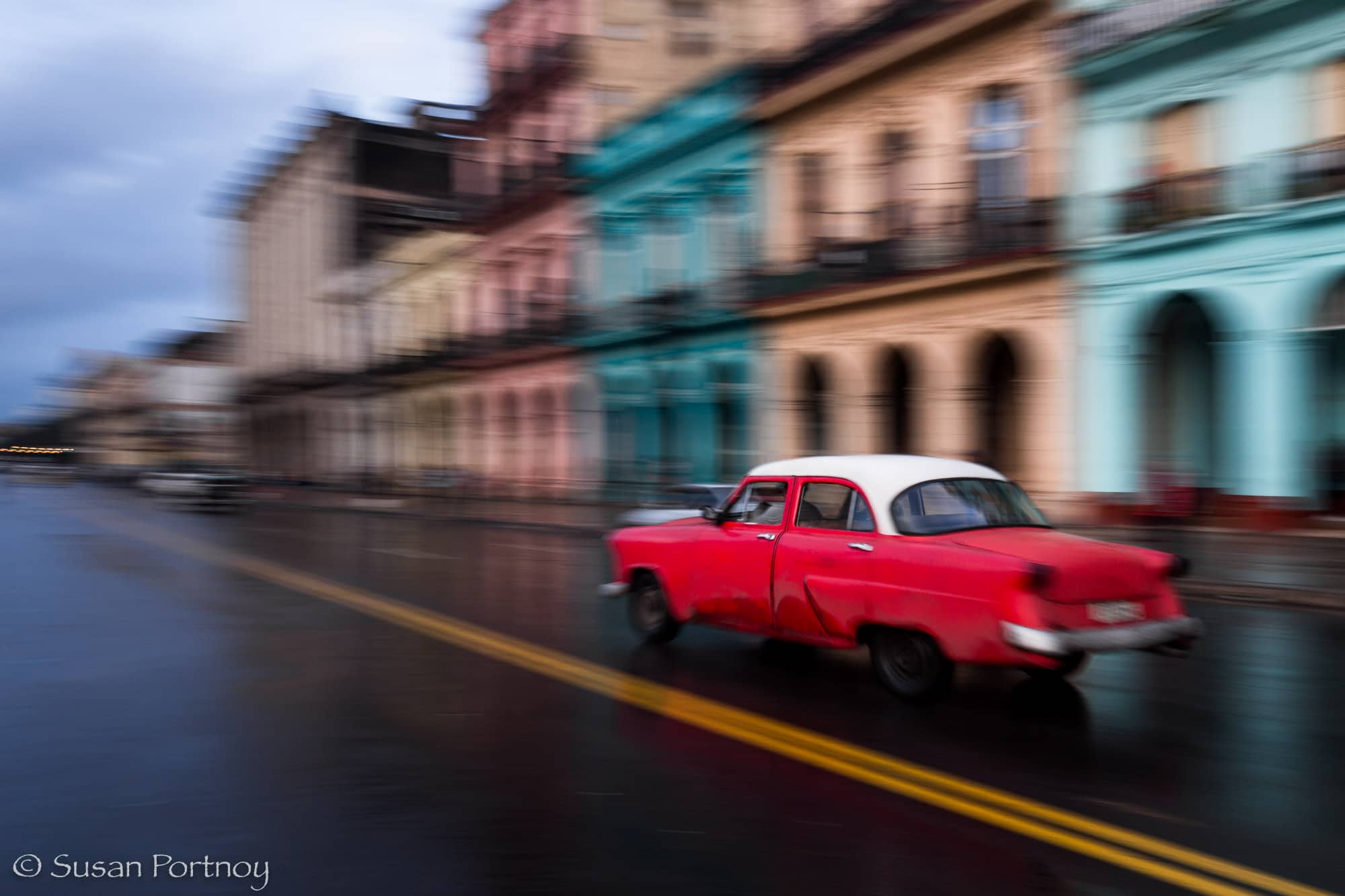 Antique car driving down a street in Havana, Cuba