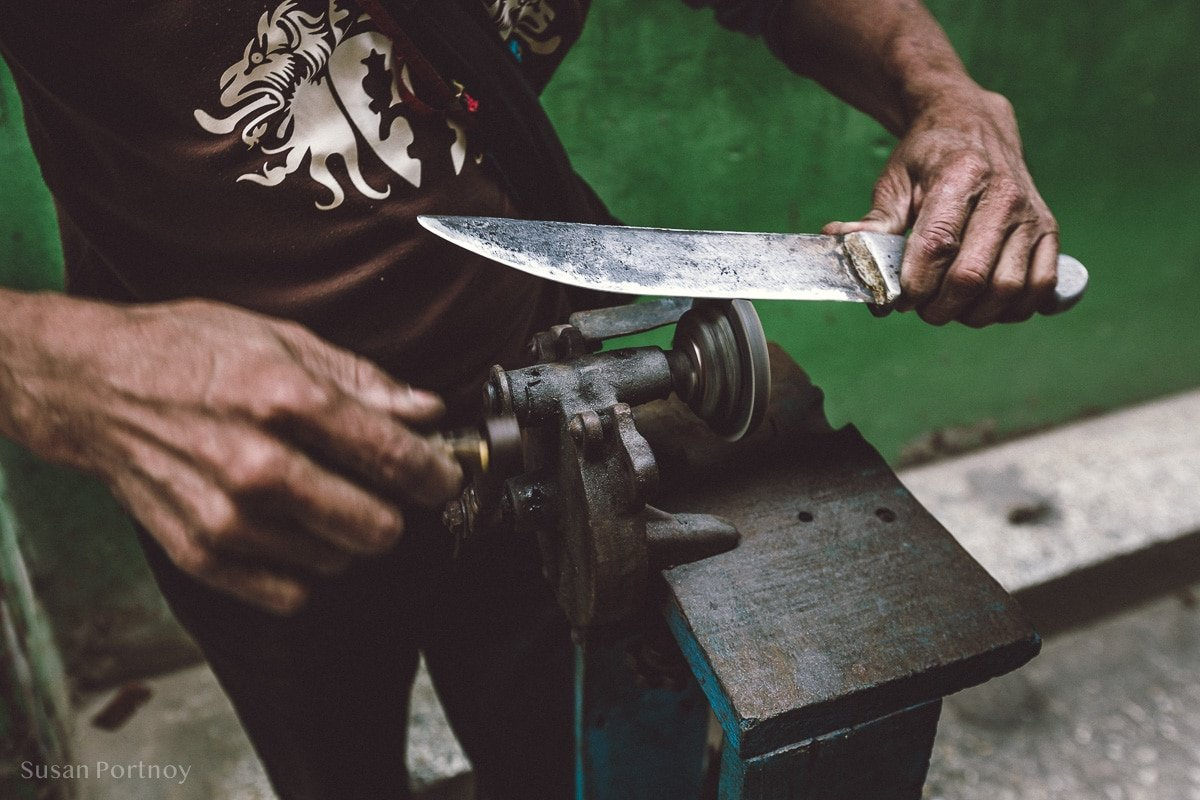 Vendor sharpens a knife on the Streets of Havana