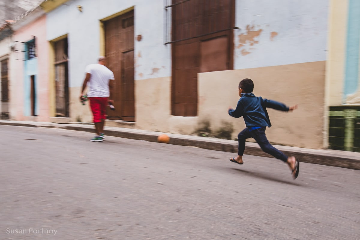 Young boy running after a soccer ball in Old Havana