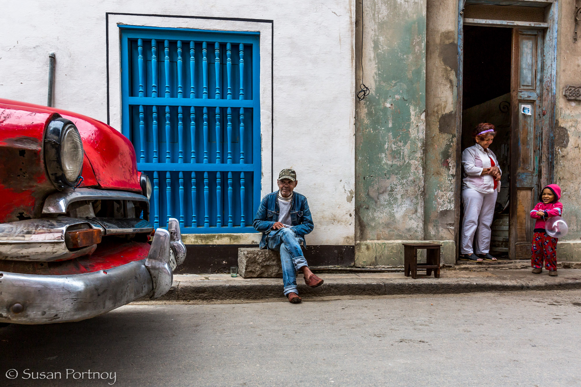 man, woman and child on a street in Havana, Cuba