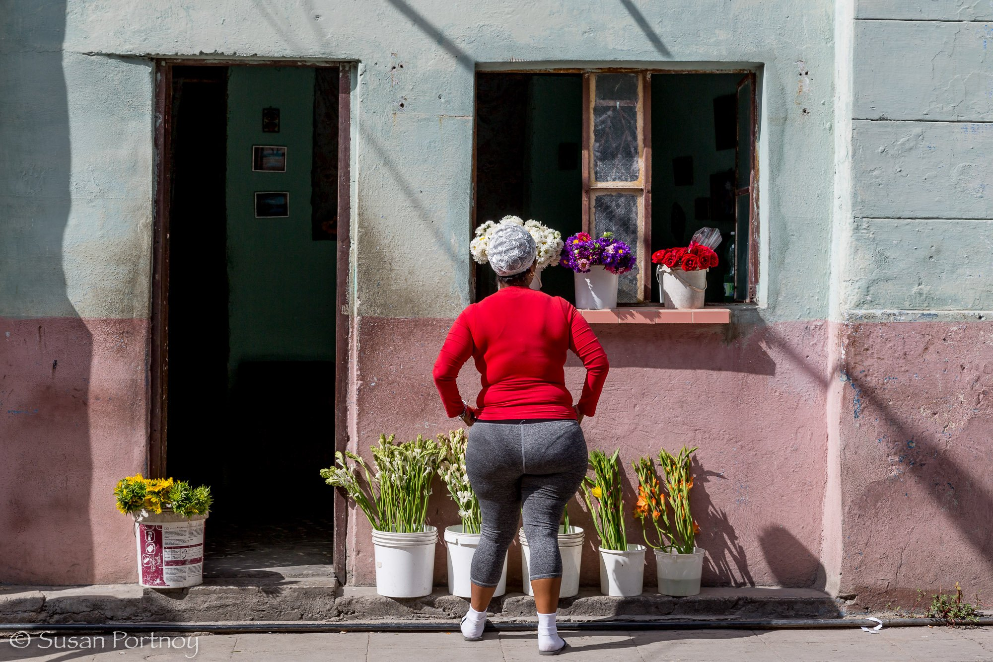Woman standing in front of her flower shop in Havana, Cuba