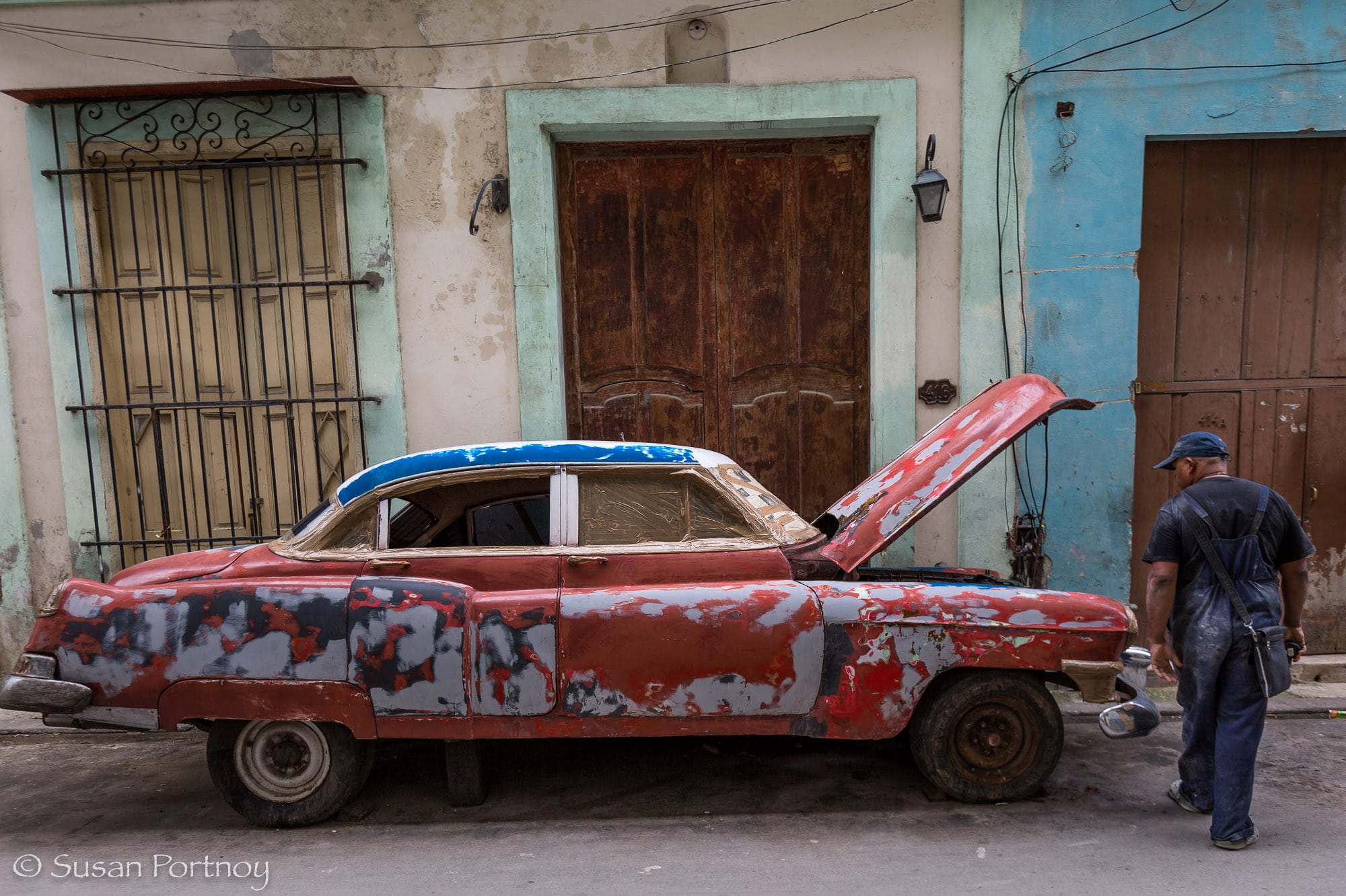 Beat up classic car driving in Havana, Cuba