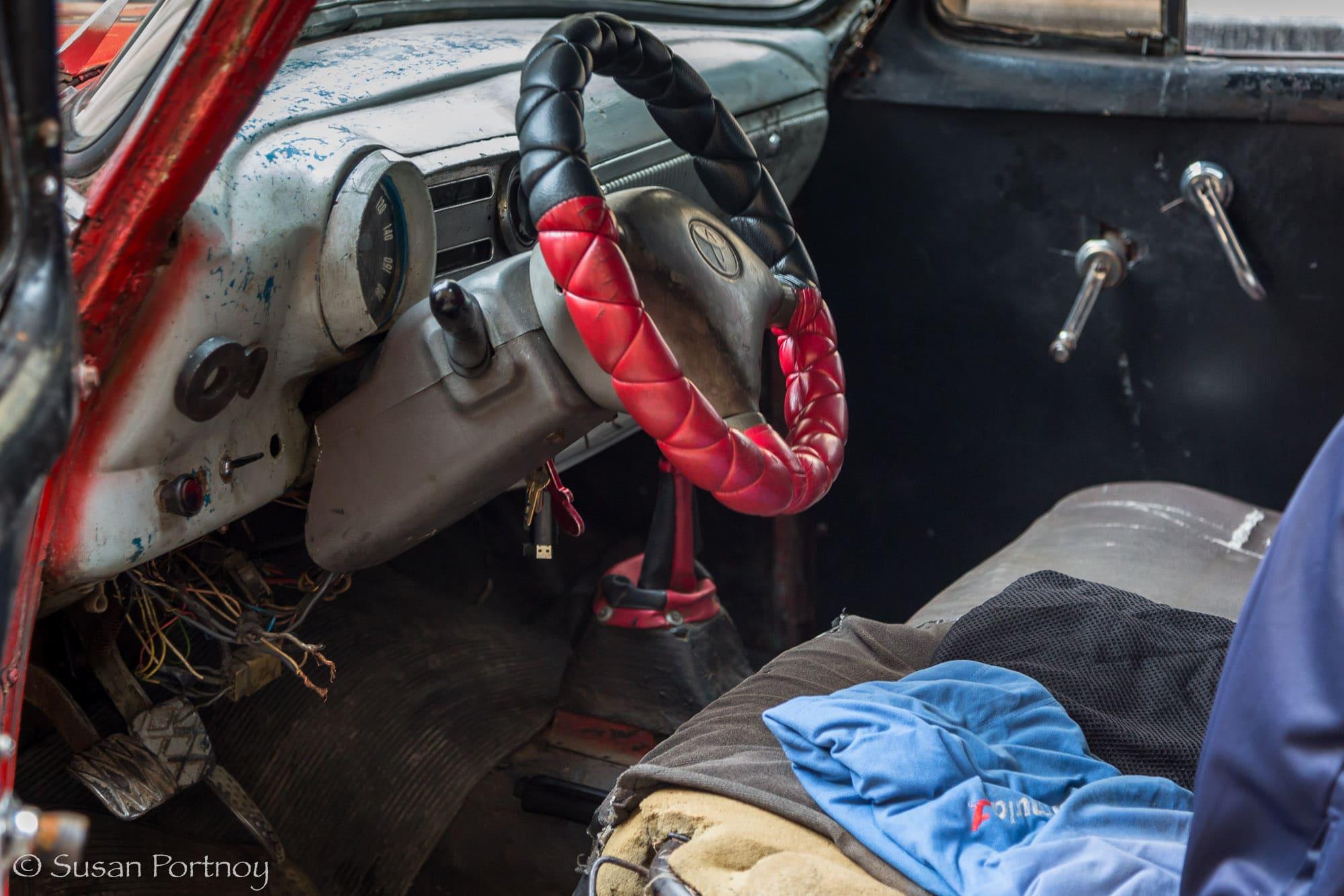 Steering wheel inside a beat up classic car driving in Havana, Cuba