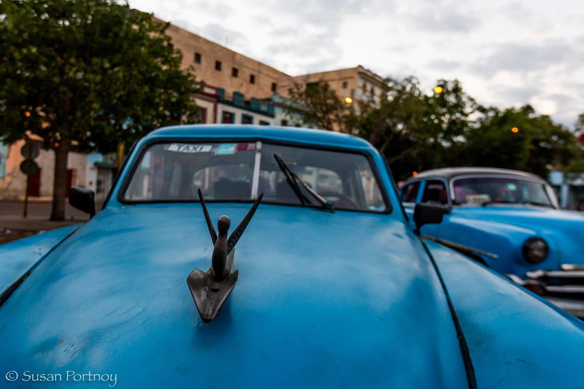 Blue classic car with sexy hood ornament in Havana, Cuba