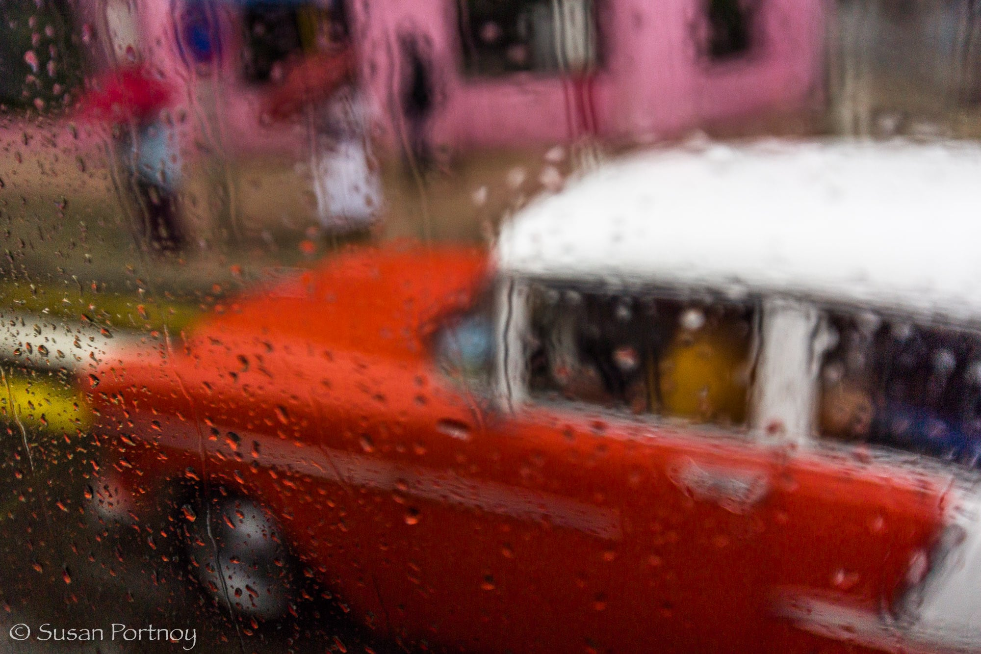 Red classic car in Havana, Cuba as seen through a rainy window
