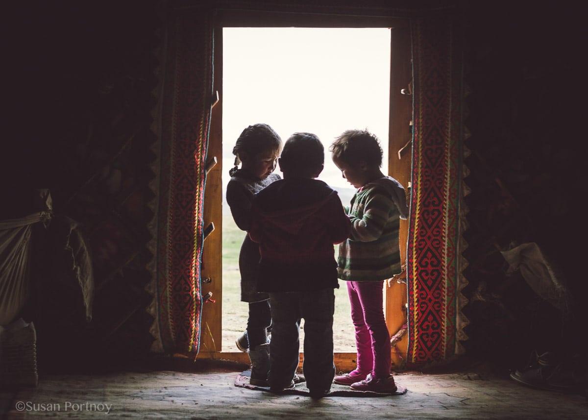 Three Kazakh children in the doorway of a ger