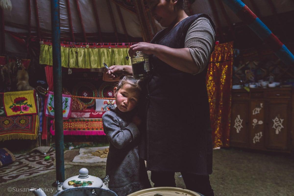 Shy little Kazakh girl hugs her mother in Mongolia
