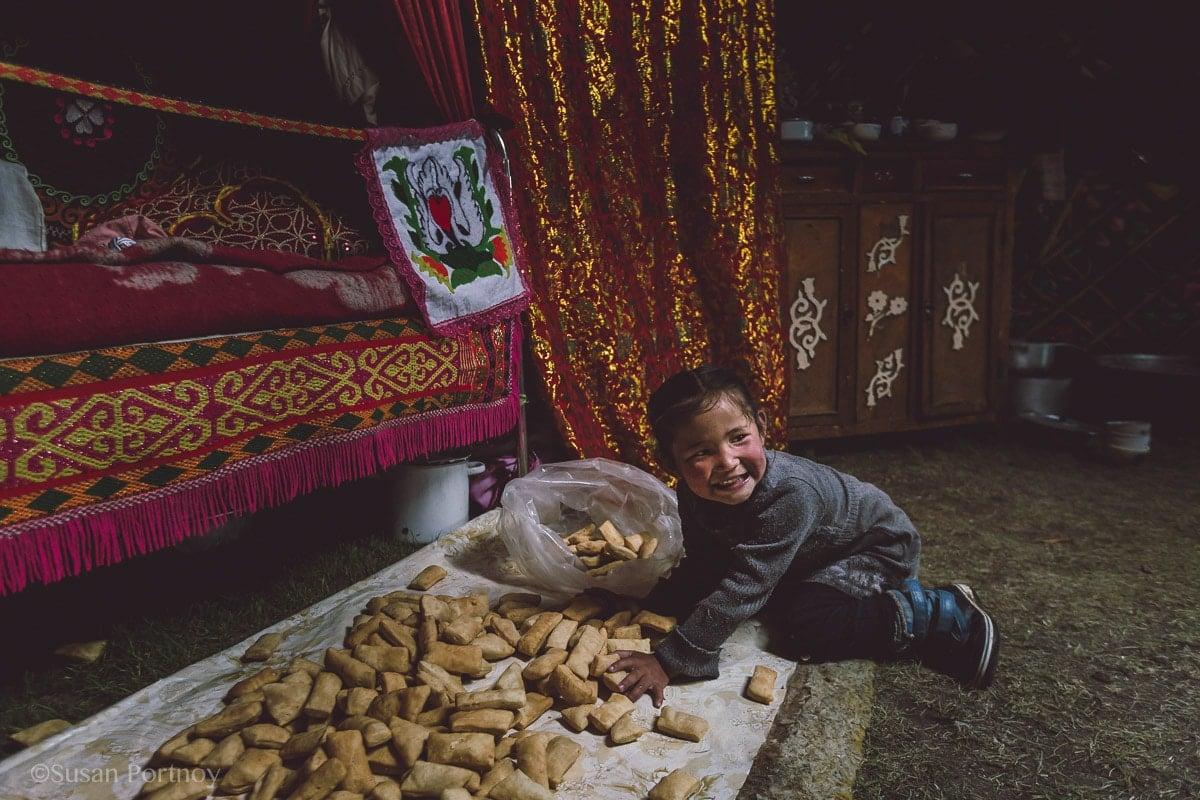 Little Kazakh girl puts Bauirsak in a plastic bag