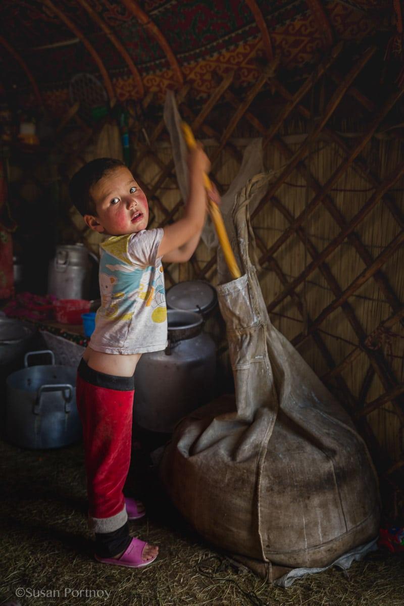 Young Kazakh girl churns butter in Mongolia