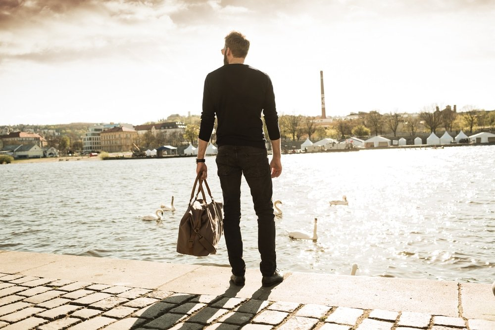 A man looking across a river with his back to the camera holding a duffle bag, and it's the first time he's traveling alone.