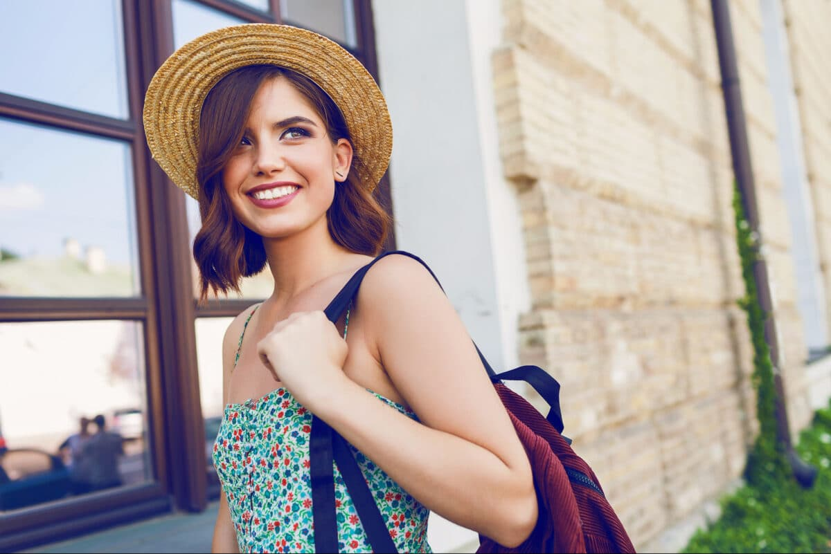 A young woman wearing a straw hat with a backpack over her shoulder about to travel for the first time alone.