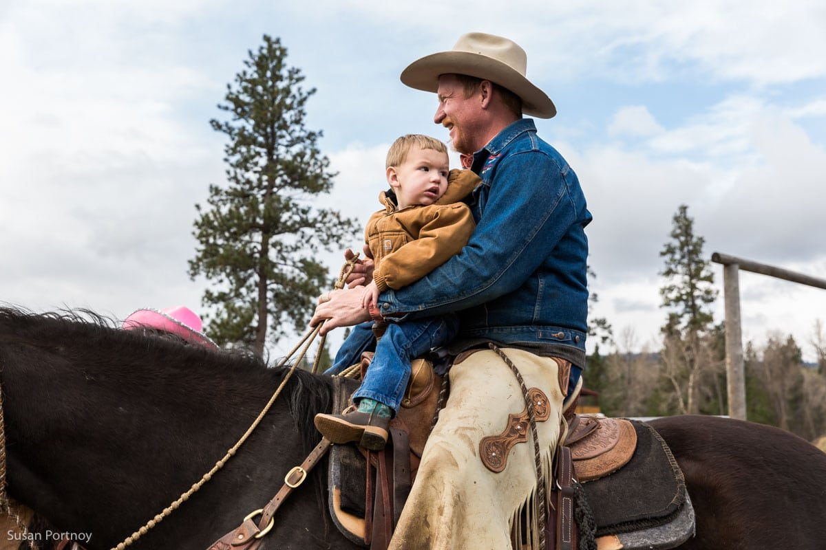 Man and toddler son riding a horse in Darby, Montana at a Triple Creek Ranch cattle branding - The Insatiable Traveler