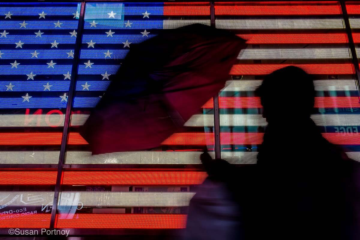 Man in silhouette with an umbrella walks past a neon American Flag screen
