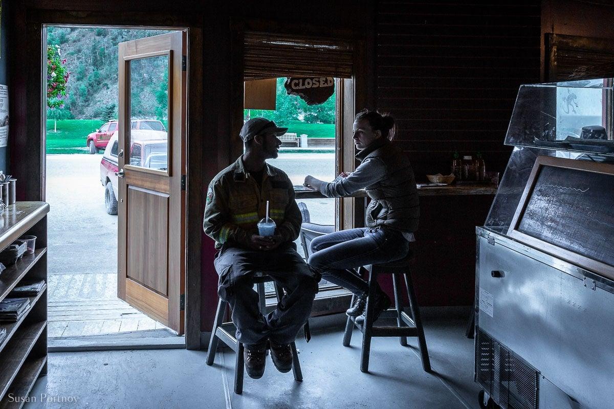 Two people in shadow talking inside CheeChakos on Front Street in Dawson City