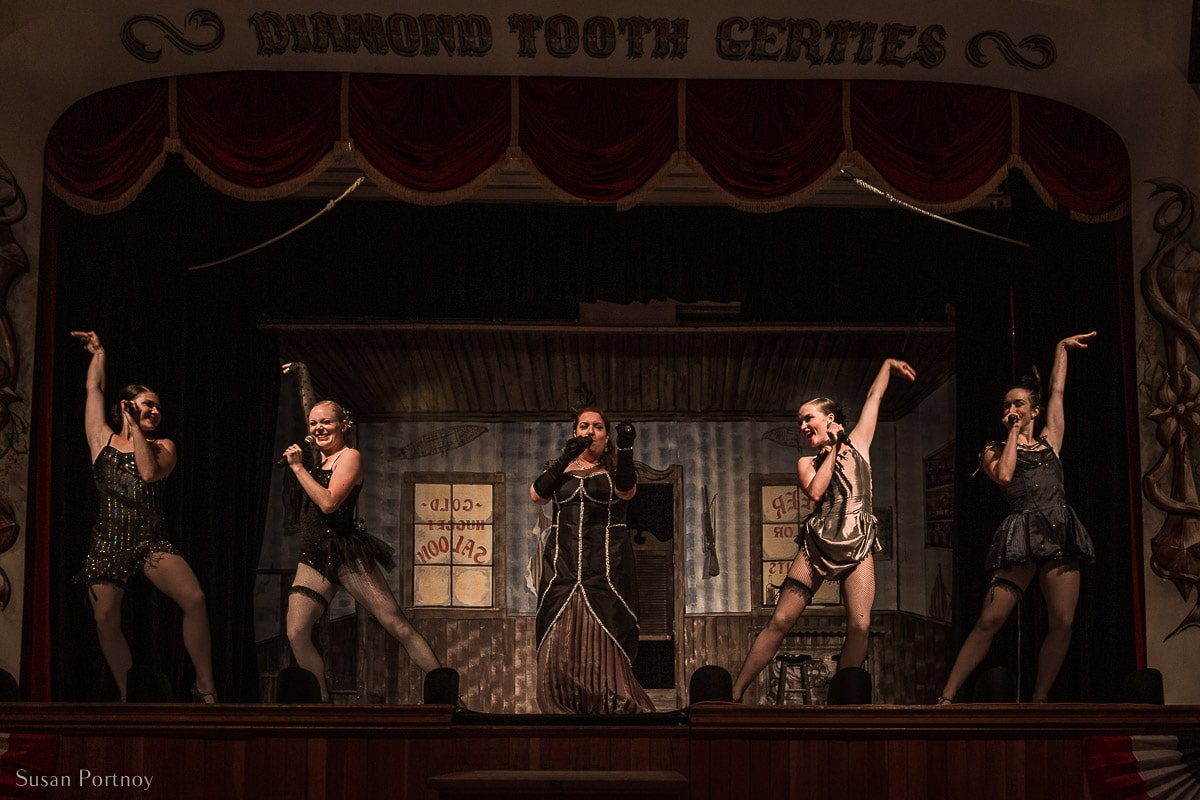 A musical performance with dancers on stage inside Diamond Tooth Gertie's Casino