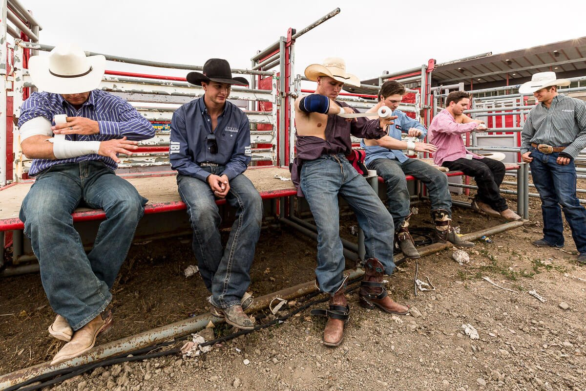 Cowboys taping up their bodies before a rodeo
