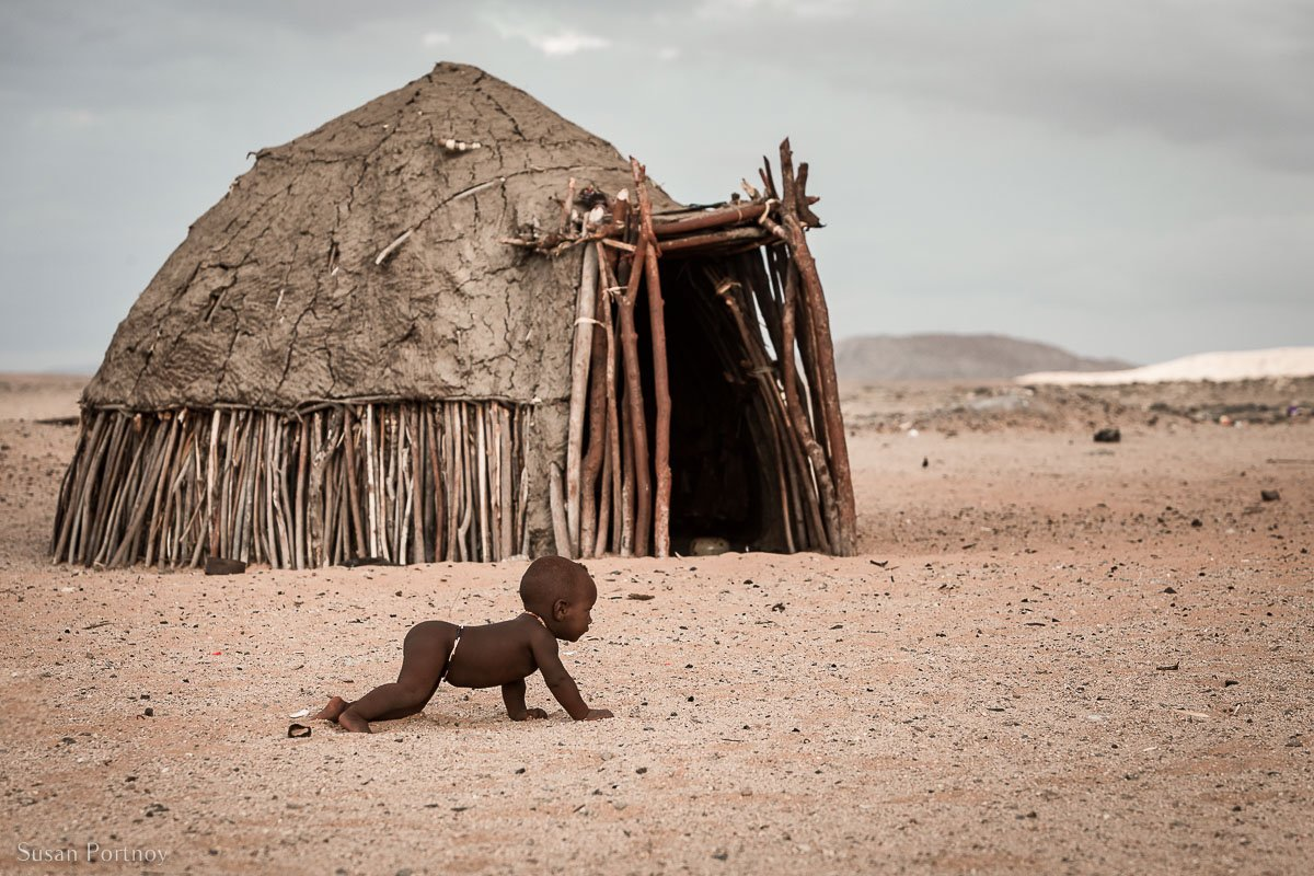 Himba baby crawling on the sand near his hut in Namibia.