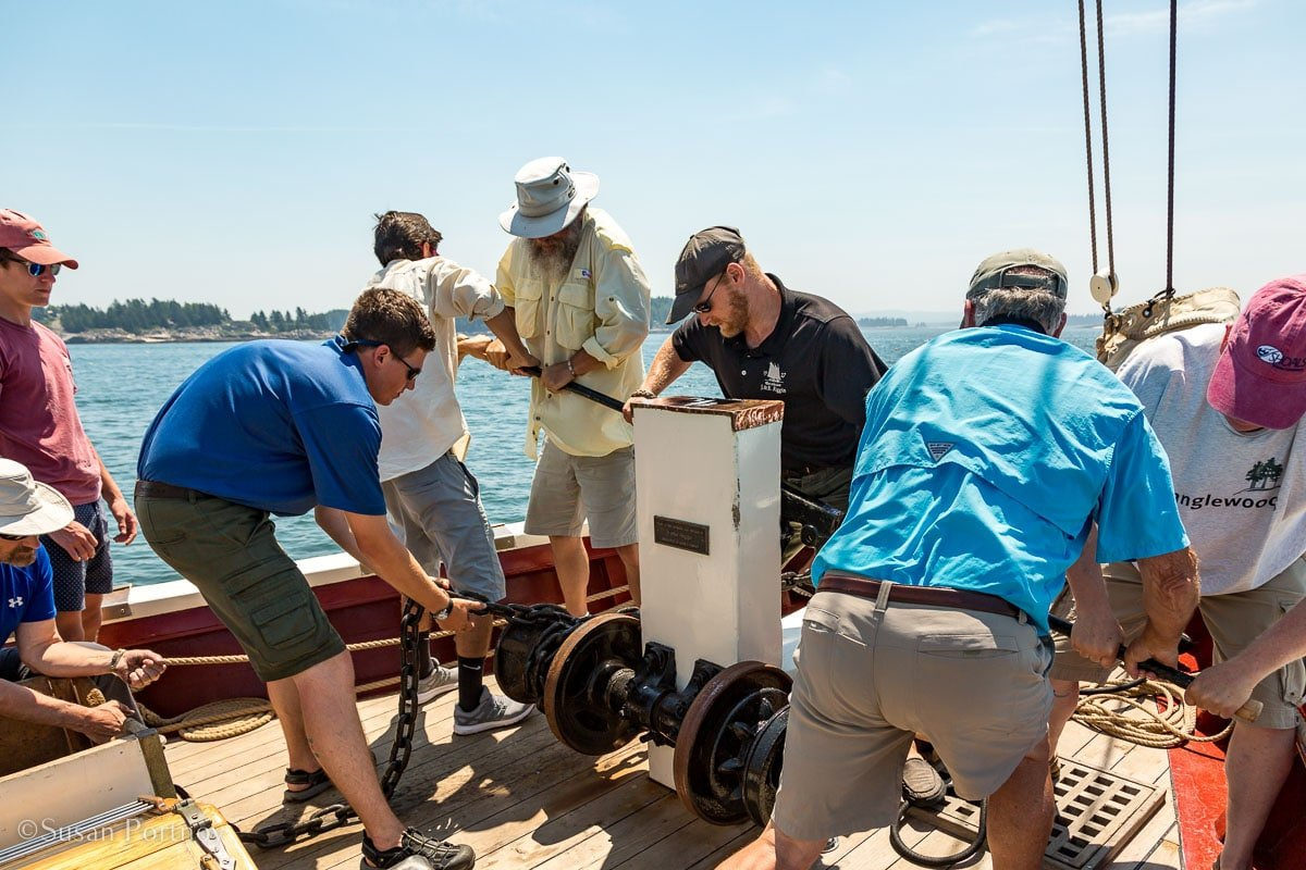 Guests and crew working the windlass on the J & E Riggin - Windjammer cruise in Maine