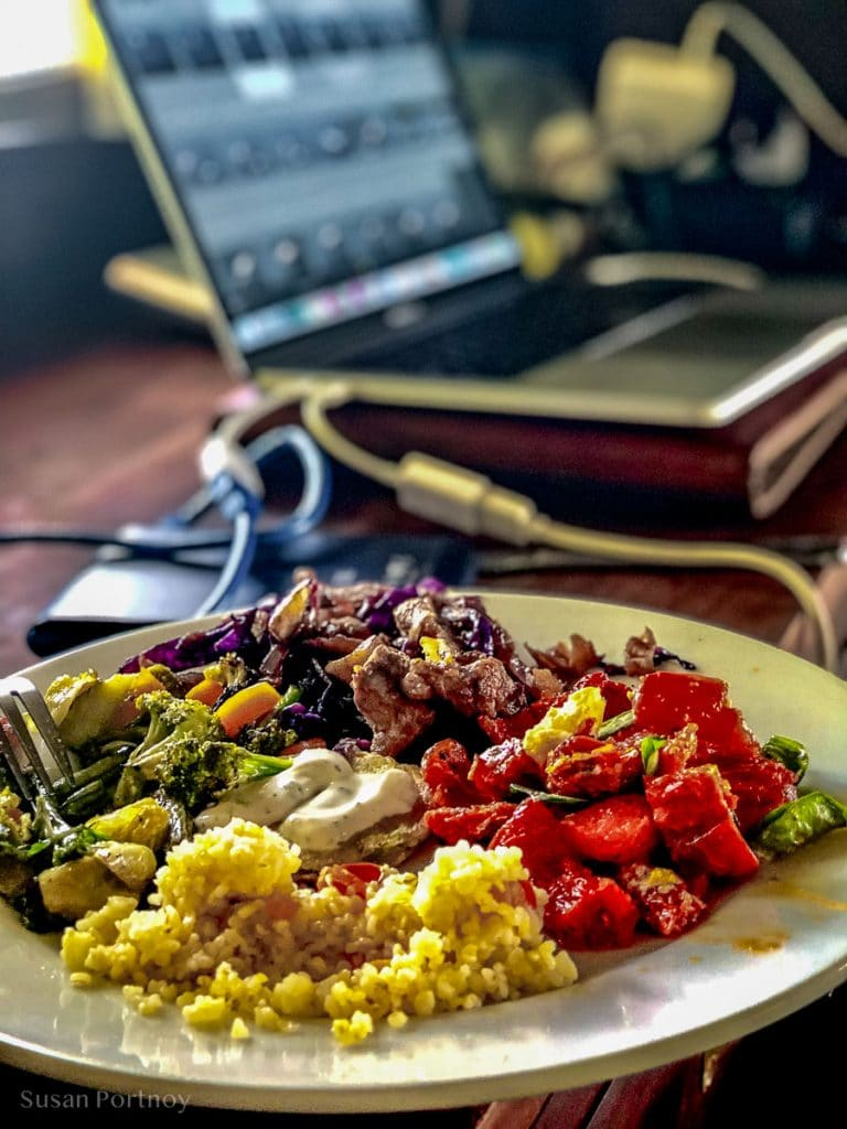 A plate filled with food and a computer in the background -