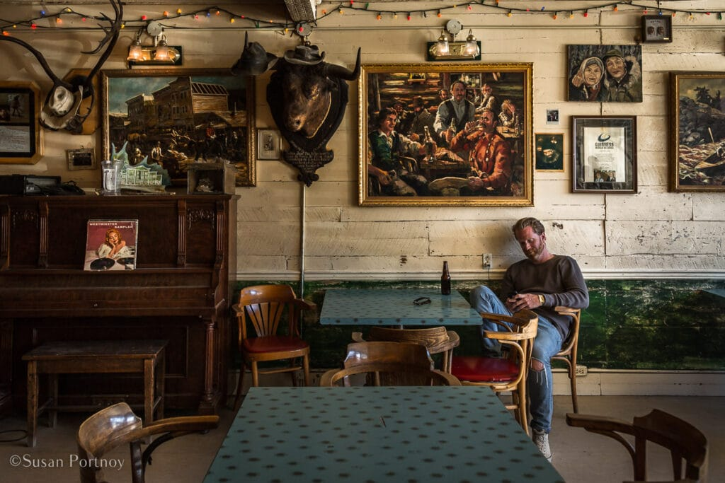 A man reads a book in the morning inside The Tavern at the Westminster hotel in Dawson City