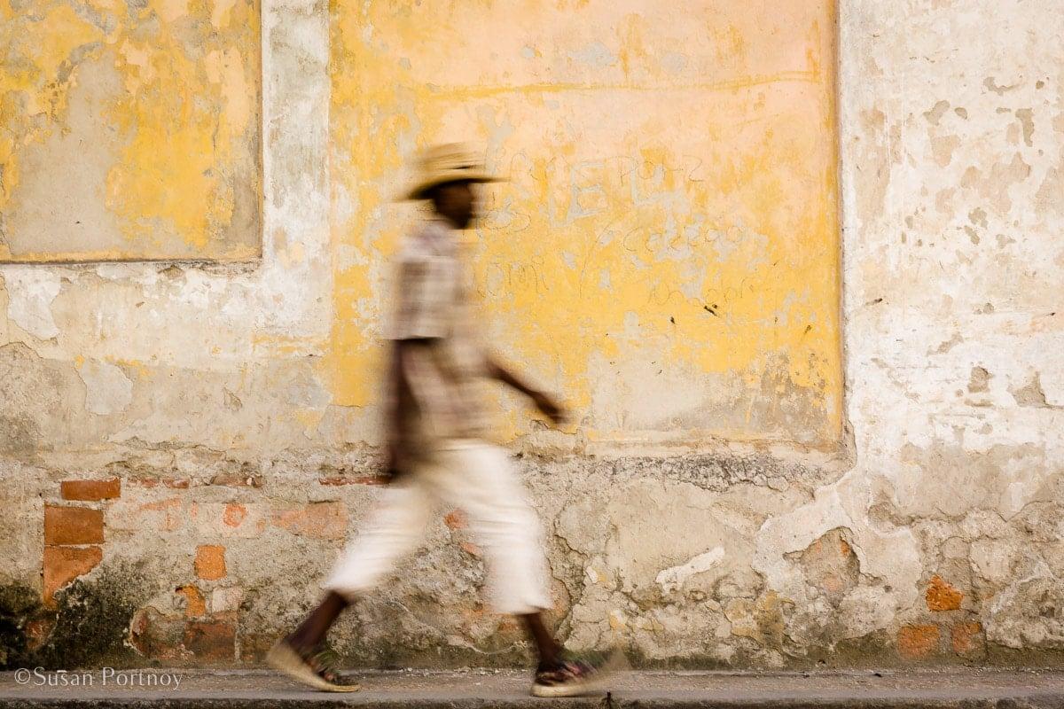 A cuban walks down a street against a yellow wall.