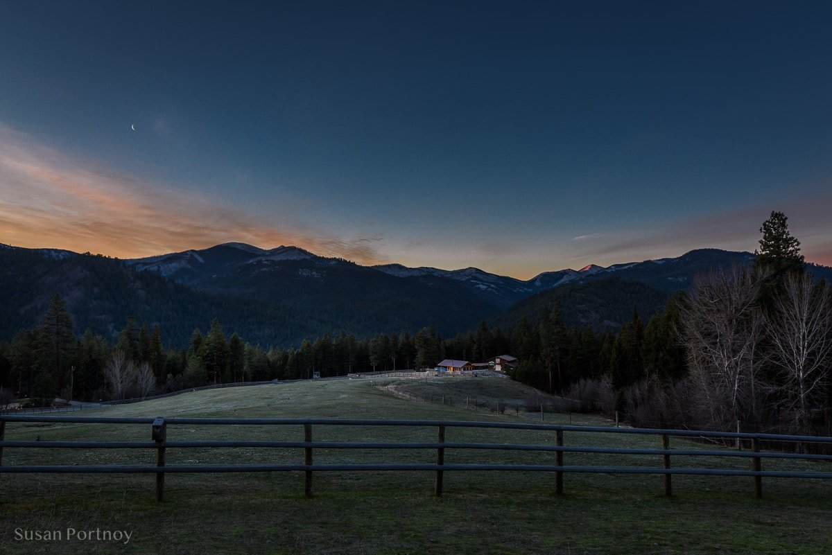 A view of a ranch with mountains in the back just before sunrise in Darby, Montana