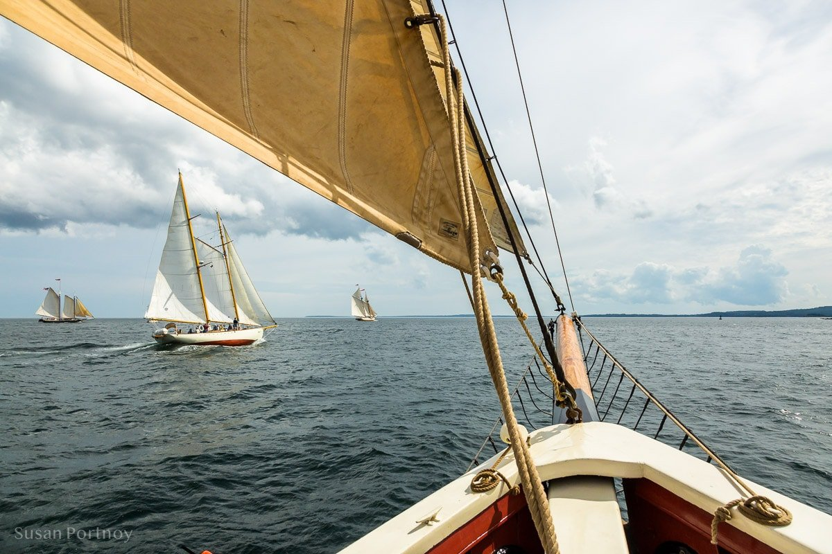 A breathtaking view of Penobscot Bay from the bow of a sailboat with other sailboats in the background
