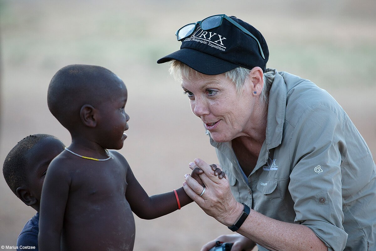 Villager and woman holding hands in Namibia