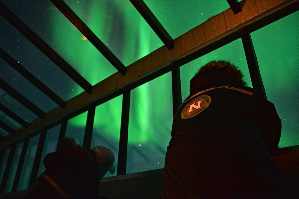 Natural Habitat Adventures - Aurora Pod with guests looking up a the Northern LIghts