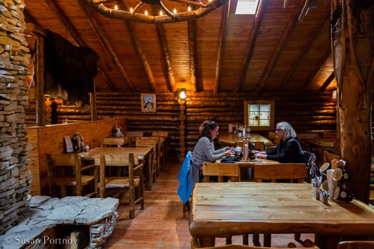 Two women eating inside the Lazy Bear Cafe, part of Lazy Bear Expeditions offering polar bear tours in Churchill