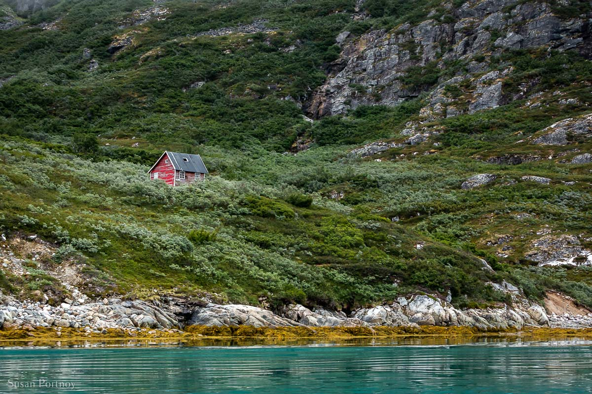 A view from a zodiac of a hut on a grassy hill in Greenland