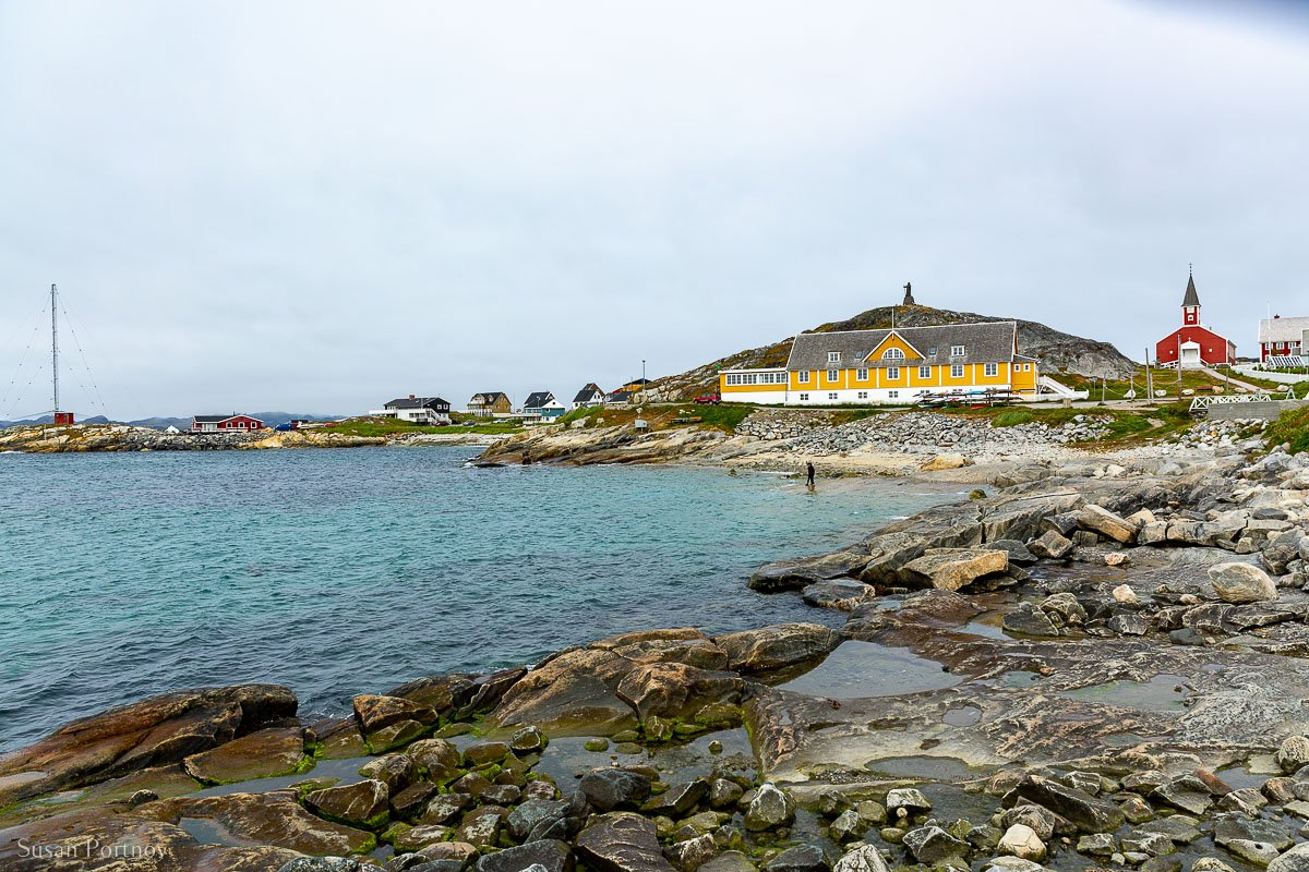 A yellow building at the edge of Nuuk beach, with a red church in the background.