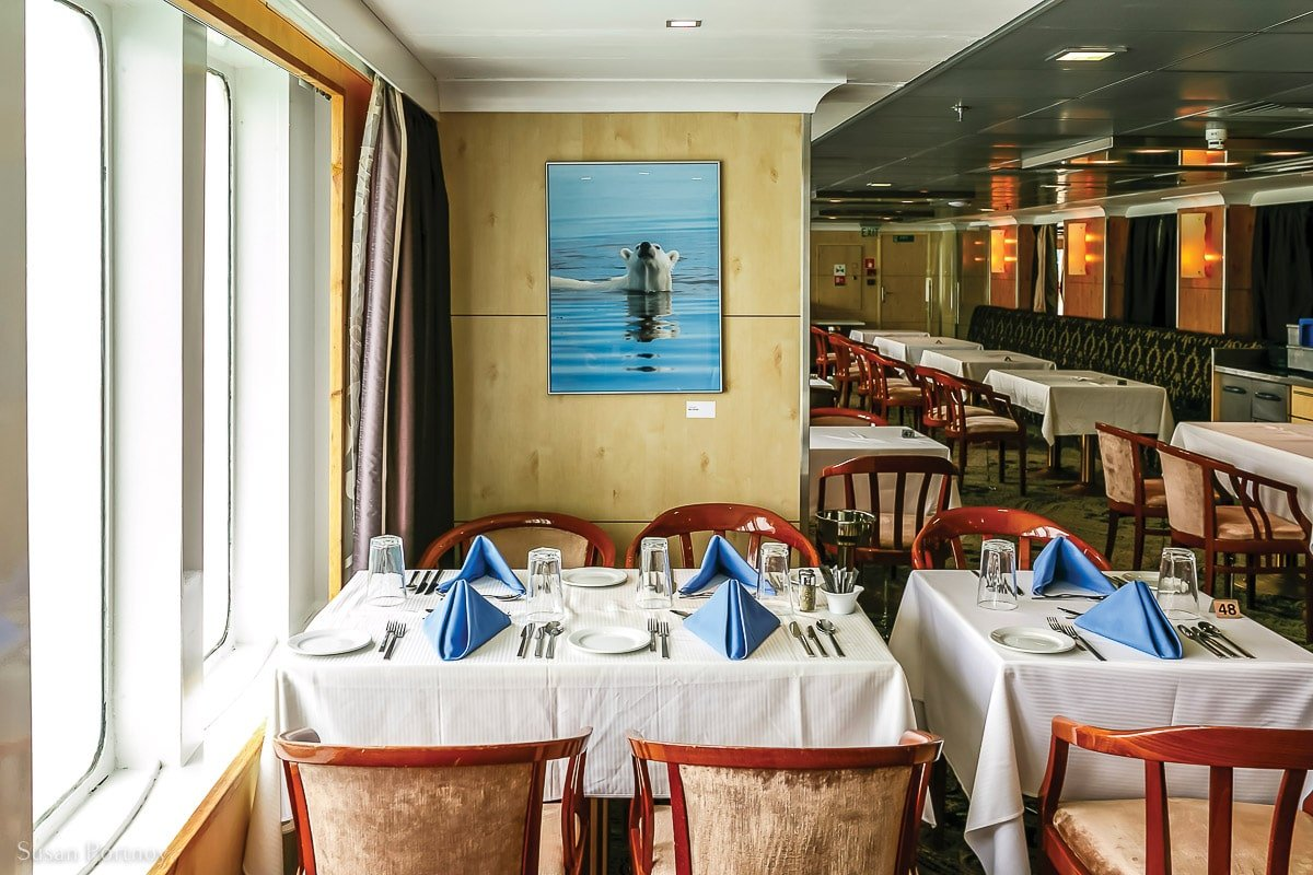 Tables next to the window in the Polaris Restaurant on the Ocean Endeavor