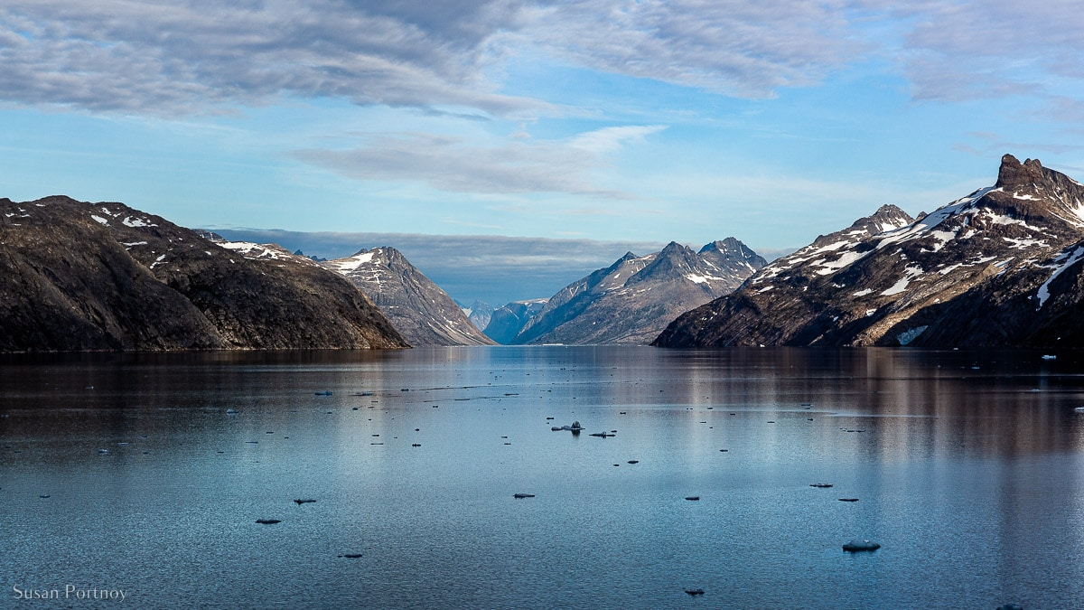 Early morning in Prince Christian Sound. A large channel of water flanked by snow-specked mountains in Greenland.