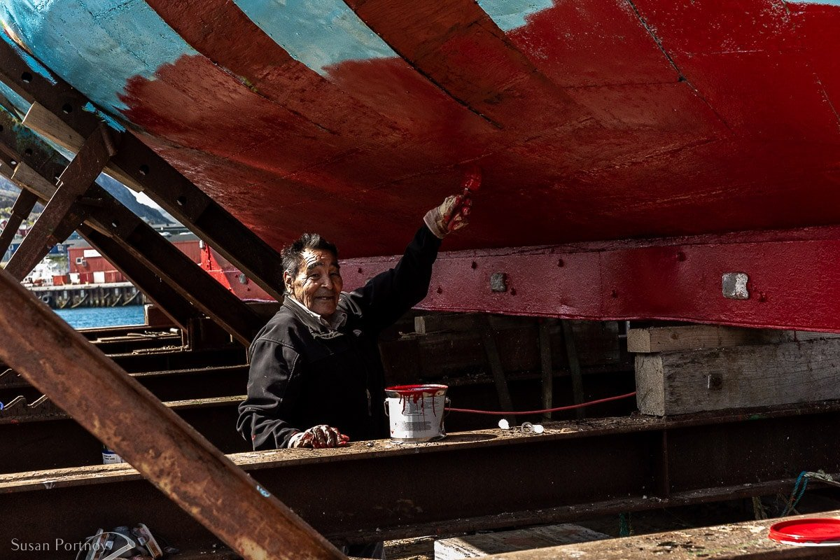 An inuit fisherman painting his boat in dry dock An Inuit fisherman painting his boat in dry dock in Qaqortoq,  Greenland