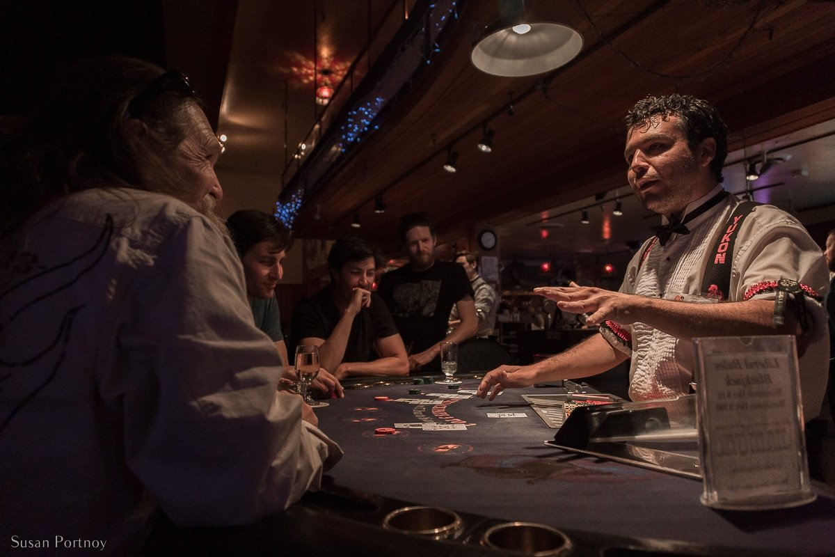 A dealer talks to a customer at a blackjack table in Diamond Tooth Gertie's Casino