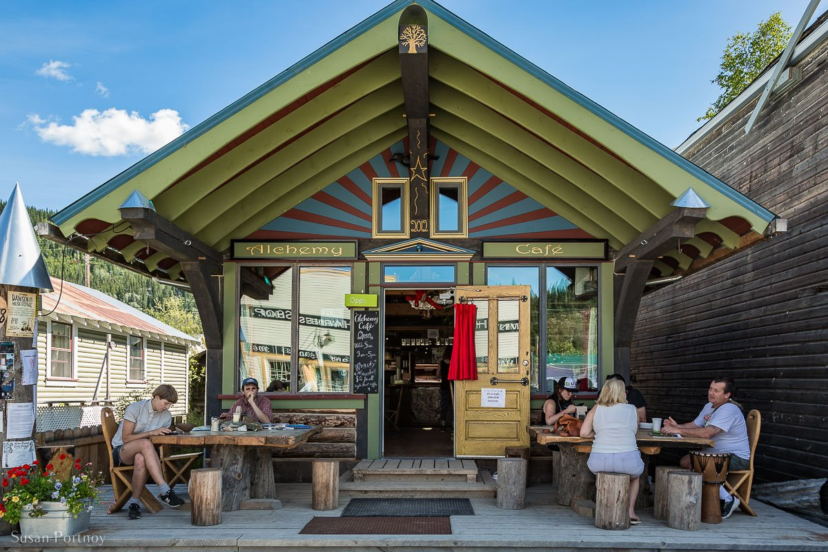 Diners sitting at picnic tables outside the Alchemy Cafe in Dawson City, Yukon