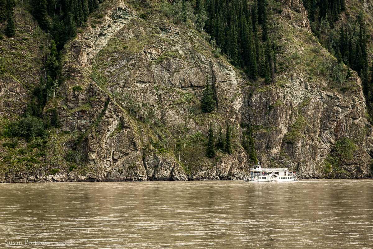 The Klondike Spirit Sternwheeler steaming down the Yukon River dwarfed by the mountains behind it.
