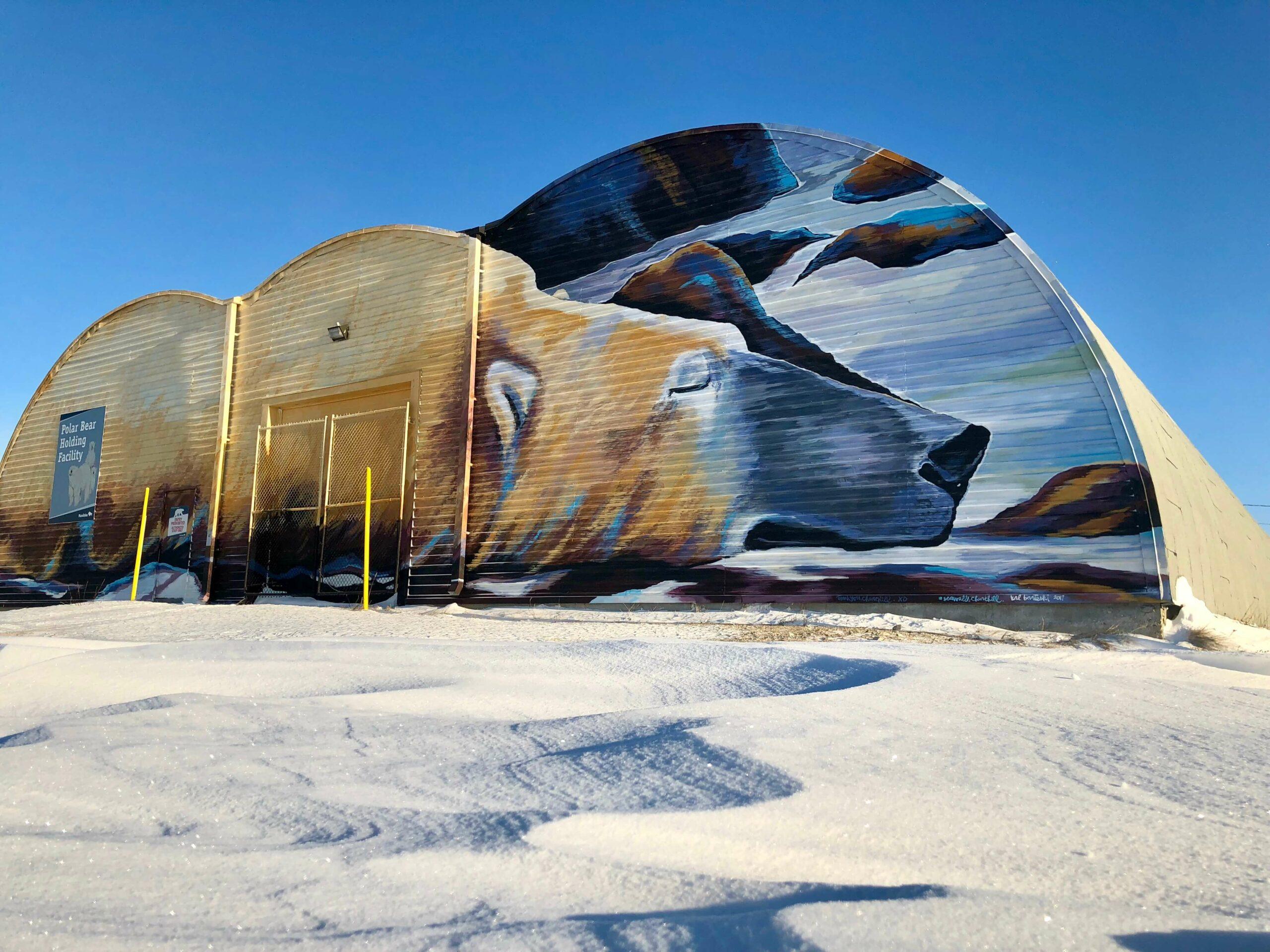 Outside of the Polar Bear holding facility decorated with a giant mural by Kal Bartesky, of a sleeping polar bear