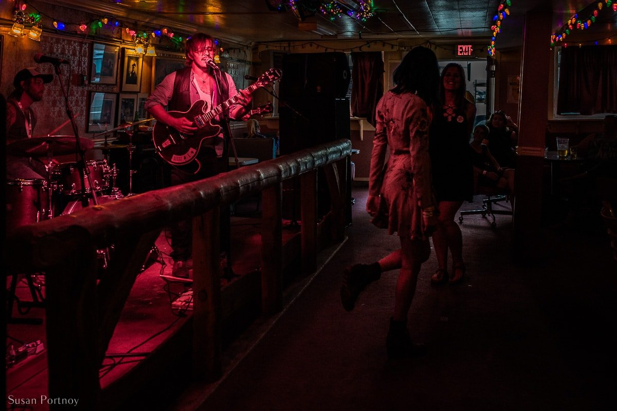 A man sings and plays guitar inside The Pit Lounge in Dawson City
