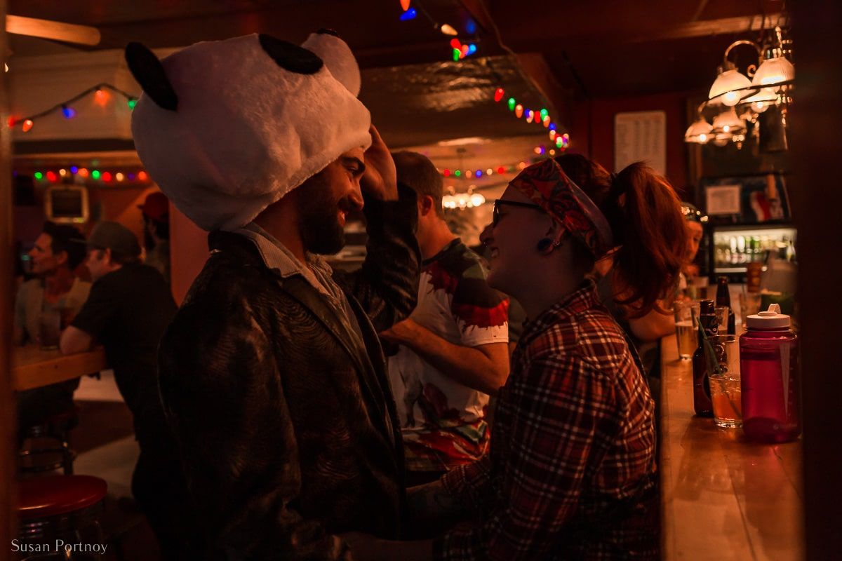 A man with a Panda Head on speaks to a woman inside The Pit Lounge in Dawson City