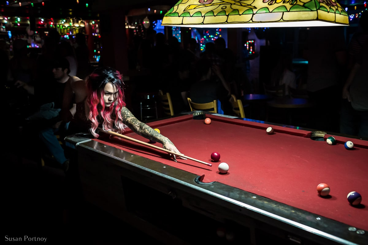 An Asian woman with long hair and tattoes plays pool inside The Pit Lounge in Dawson City, Yukon