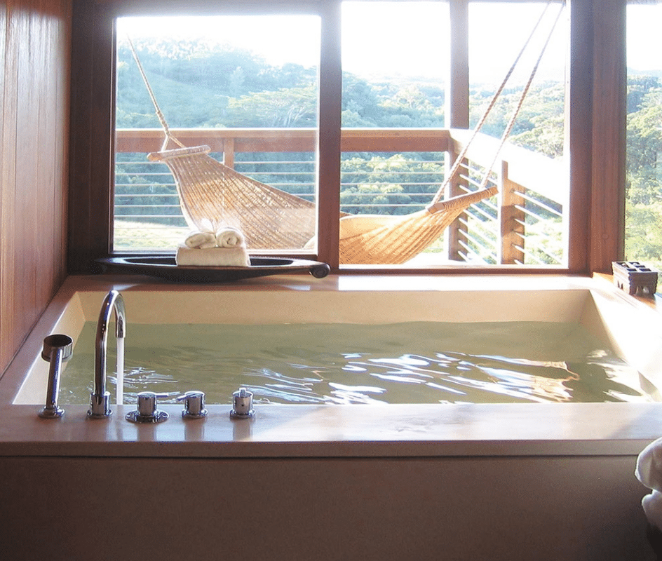 View of a large full tub next to a beautiful window at the aO' Louina (The Longhouse), Kauai. One of 7 unique places to stay in Hawaii