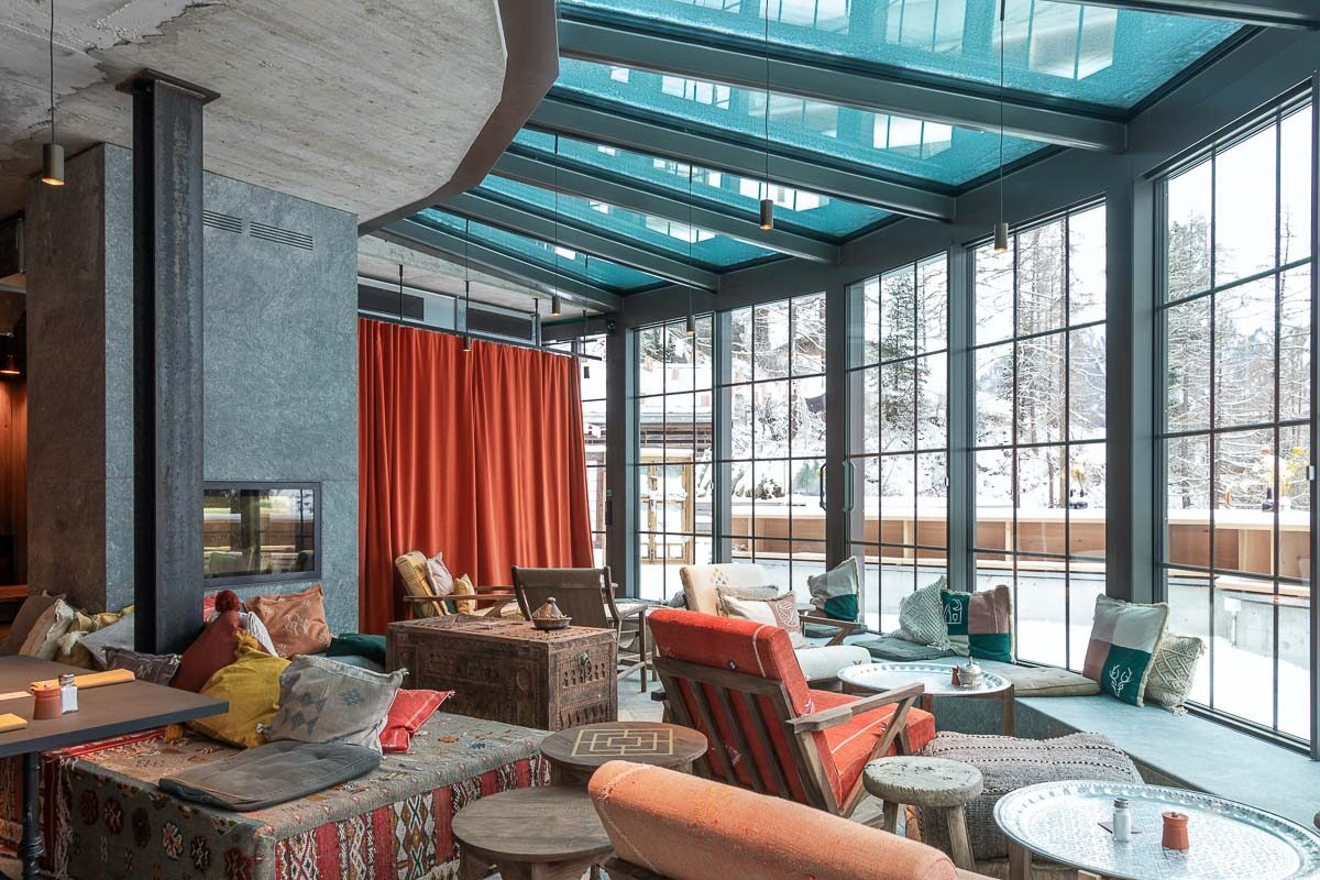 Cervo Mountain Resort - Large toom with floor to ceiling windows  revealing mountain views