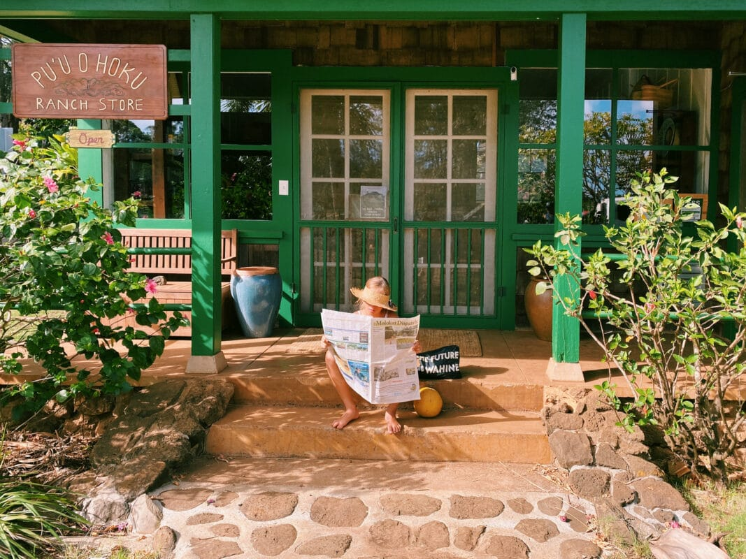 Female sitting outside in front of french doors and the entrance to a suite at the Pu'u O Hoku Ranch, Molokai - a very cool place to stay in Hawaii