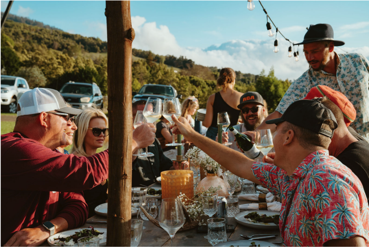 Many people at a table outdoors during a Kiawe Outdoors experience