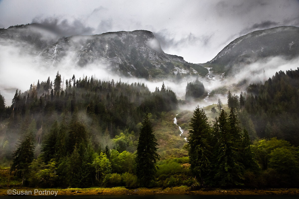Mountains covered in mist under cloudy skies. It's important to have a good packing list for British Columbia